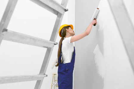 Young female worker painting wall in room