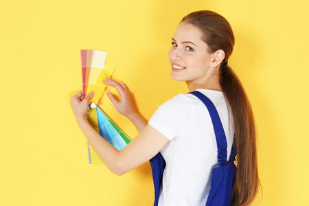 Beautiful young decorator selecting color of wall, on yellow background Banque d'images