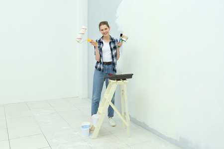 Beautiful young woman making repair in room Banque d'images - 109934749