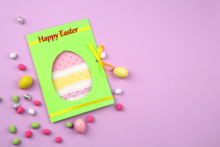 Easter concept. Greeting card and colourful eggs with candies on purple background Stock Photo