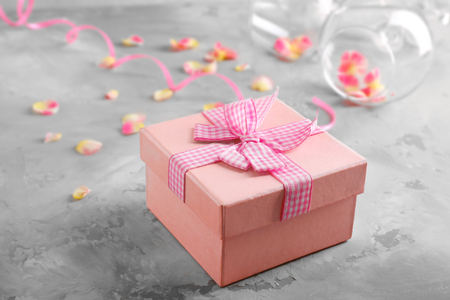 St. Valentines Day concept. Gift box, petals and empty wine glasses on table