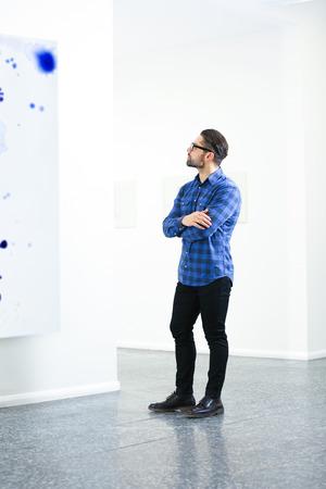 Young man in modern art gallery Banco de Imagens