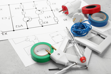 Electrician tools and schemes on grey background