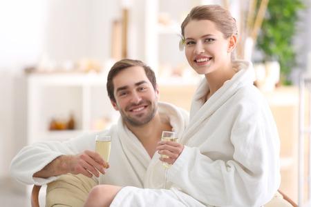 Junges glückliches Paar, das Champagner im Spa-Salon trinkt