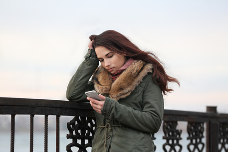 Depressed young woman with phone on pier Standard-Bild