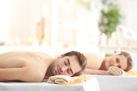 Joven pareja feliz relajante en el salón de spa