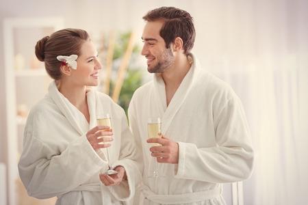 Jonge gelukkige paar champagne drinken in spa salon