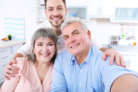 Young man with middle aged parents taking selfie Stock Photo