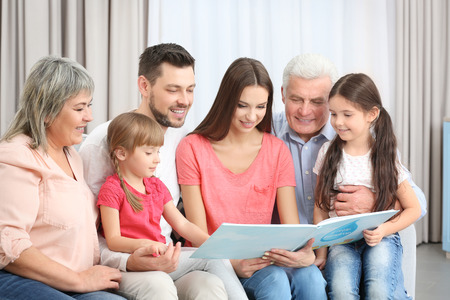 Happy family with book sitting on sofa in the room