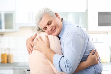 Middle aged couple embracing at kitchen