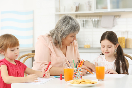 Little girls with grandmother drawing at kitchen table Banque d'images