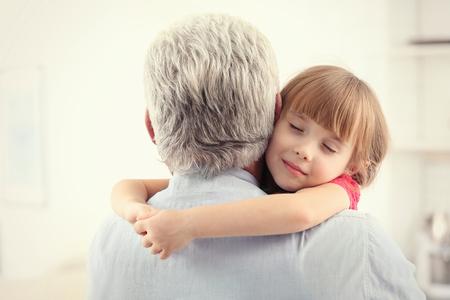 Fille embrassant le grand-père à la maison