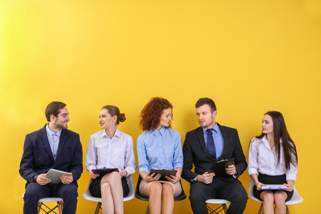Group of people waiting for job interview on yellow wall background Stock Photo