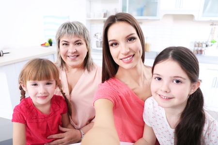Mother, granny and girls taking selfie at kitchen Banque d'images