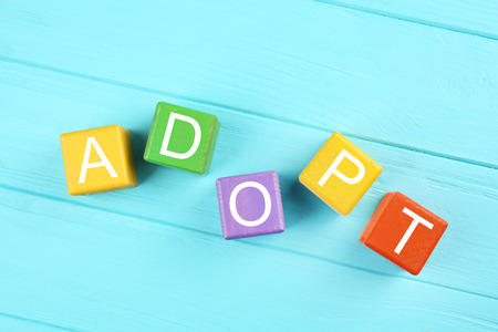 Bunte Würfel mit Wort ADOPT auf hölzernem Hintergrund Standard-Bild