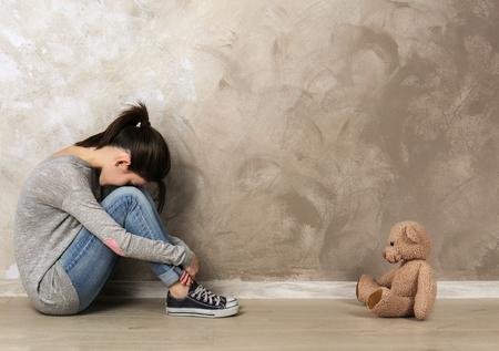 Kleines Mädchen, das mit Spielzeugbär auf Farbwandhintergrund sitzt