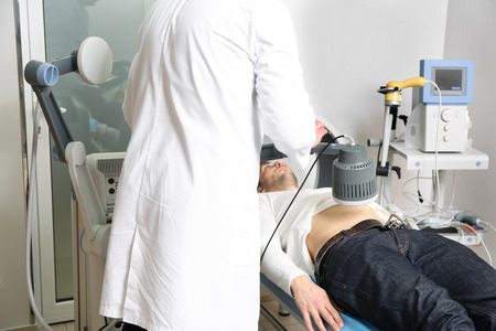 Inductive shortwave diathermy for young man in modern clinic