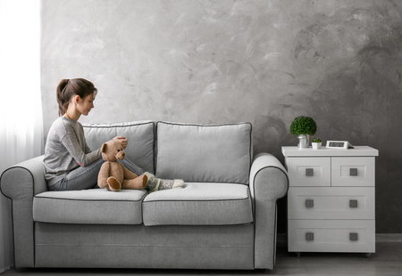 Little girl with toy bear on sofa in room Stock Photo