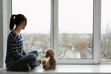 Little girl with toy bear on windowsill Standard-Bild