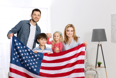 Happy family with American flag at home