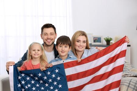 Familia feliz con bandera americana en casa