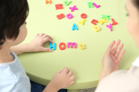 Little boy with teacher constructing word HOME on private lesson