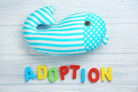 Word ADOPTION and whale toy on light wooden background