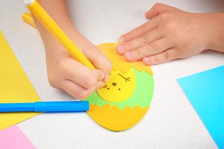 Hands of child making Easter application while sitting at table Reklamní fotografie