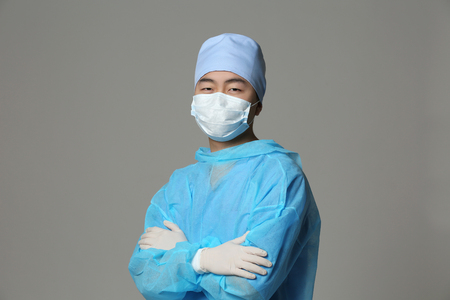 Young Asian doctor on grey background