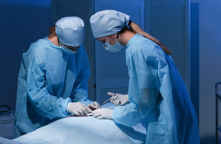 Surgeons operating patient in clinic