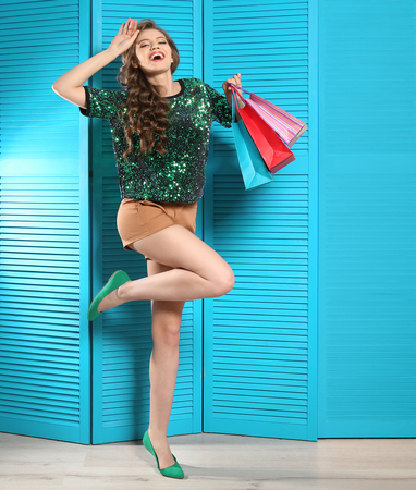 Young woman with shopping bags in dressing room Stock Photo