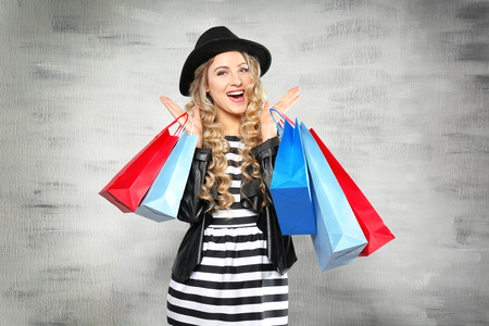Woman with shopping bags on light background Stock Photo