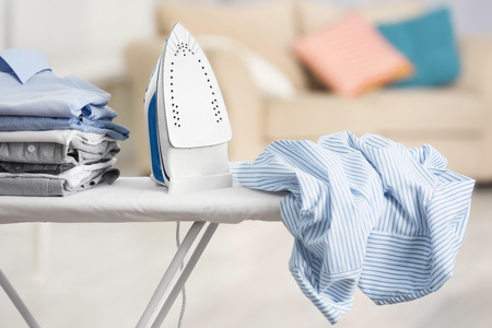 Electric iron and pile of clothes on ironing board Stockfoto