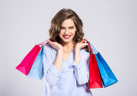 Woman with shopping bags on light background 스톡 콘텐츠