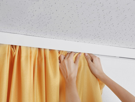 Woman hands installing curtains over window Foto de archivo