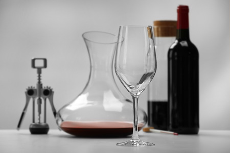 Glass and decanter on table against light background