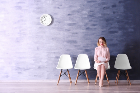 Young woman waiting for job interview in reception hall Imagens