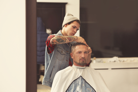 Barber making modern male hairstyle Imagens