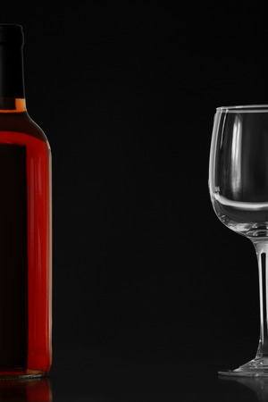 Bottle of red wine and glass on black background Foto de archivo