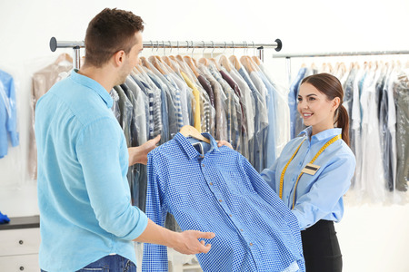 Woman working with customer in dry-cleaning salon Imagens