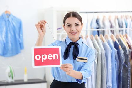 Female worker holding board in dry-cleaning salon Stock fotó