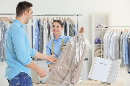 Woman working with customer in dry-cleaning salon Archivio Fotografico