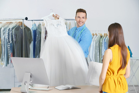 Man working with customer in dry-cleaning salon