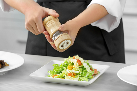 Female chef hands with pepper mill over plate with fresh salad