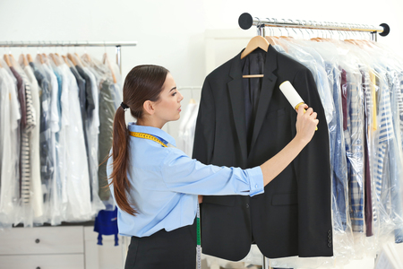 Woman with adhesive roller cleaning clothes in dry-cleaning salon 免版税图像