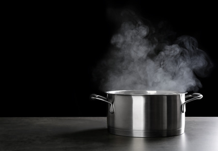 Metal saucepan with hot liquid on table against dark background 写真素材