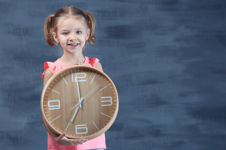 Cute little girl with big clock near color wall