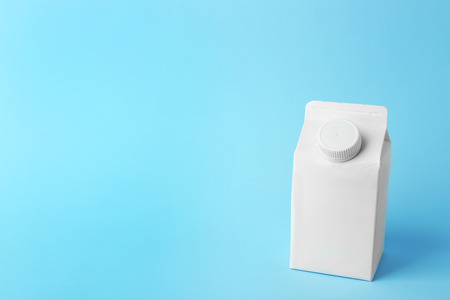 Simple milk box on color background 版權商用圖片