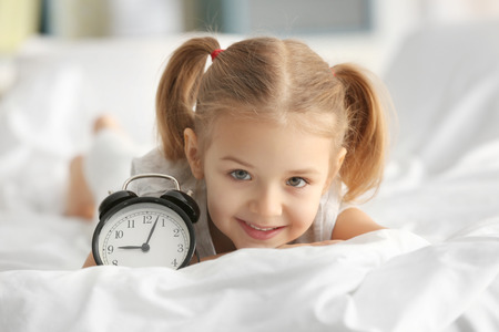 Cute little girl with alarm clock lying on bed