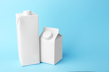 Two simple milk boxes on color background